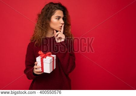 Photo Shot Of Beautiful Positive Young Brunette Curly Woman Isolated Over Red Background Wall Wearin