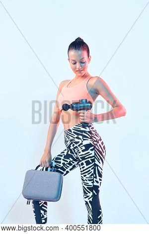 Percussion Massager, Athletic Young Fit Female Showing Handheld Massaging Gun In Neon Studio Light