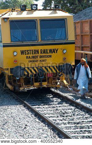 Gujarat, India-january 29, 2010: Train And Indian Man Walking Through The Railroad Tracks.