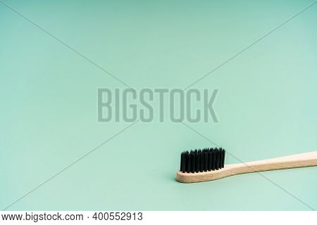 Eco Friendly Antibacterial Bamboo Wood Toothbrush With Black Bristles On Light Green Background. Tak