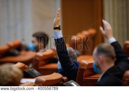 Bucharest, Romania - December 22, 2020: Romanian Deputies Vote Bills By Raising Their Hands In A Ful