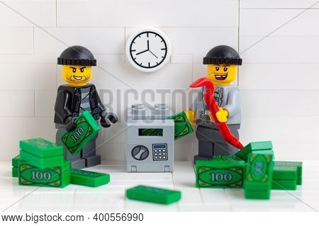 Tambov, Russian Federation - December 22, 2020 Two Lego Minifigure Robbers Stealing Money From A Saf