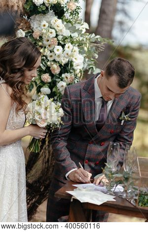 Groom Signing Wedding Papers And Bride Looking At Him At The Wedding Ceremony. Happy Newlyweds