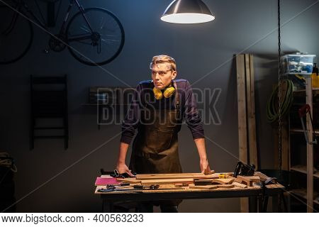 A Young Carpenter In An Apron Works In A Carpenters Shop, Making Wood Products
