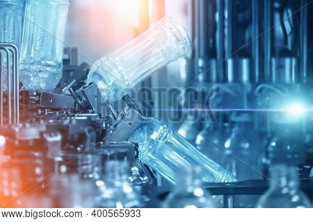Abstract Industrial Background In Blue Color With Filling Plastic Bottles Inside Industrial Machine