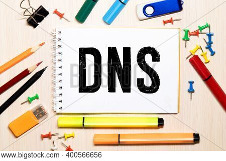 Dns, Domain Name System, Text On White Card Next To Notepad And Pen On Table.