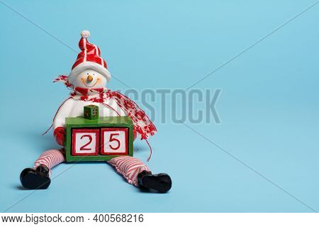 A Snowman Figure Is Holding A Box With Two Cubes Forming A Number Twenty-five. It Is December The Tw