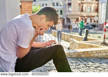 Boy Teenager 16, 17 Years Old, Using Smartphone, Sitting On Street Of Summer City. Copy Space, Guy R