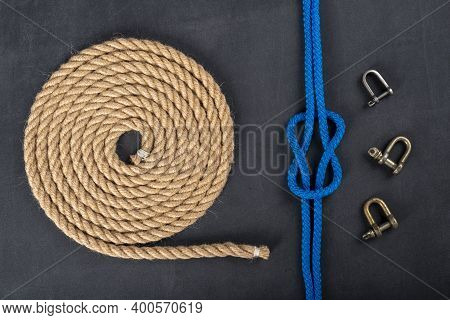 Thick Jute Rope Coiled In The Shape Of A Circle, Shackles And A Simple Knot. Sailing Accessories Use