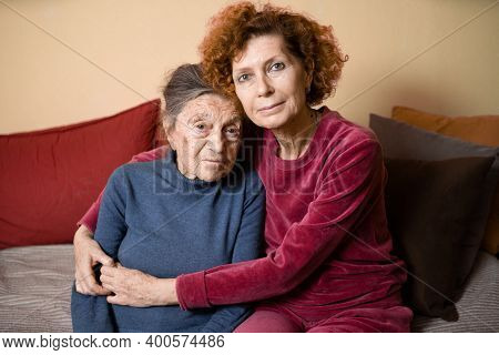 Senior Caucasian Woman Tenderly Hugs Her Ninety Year Old Elderly Mother With Gray Hair, Face With De