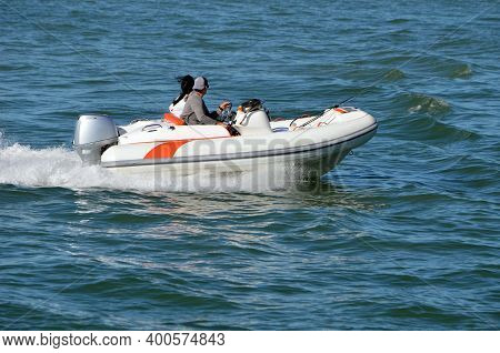 Sporty Two Seater Pontoon Motorboat Powered By A Single Outboard Engine.