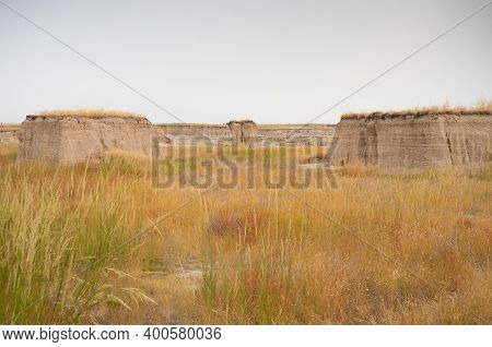 Grass-topped Buttes Or Plateaus In A Prairie With Tall Grass. Photographed In Badlands National Park