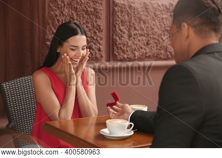 Man With Engagement Ring Making Proposal To His Girlfriend In Outdoor Cafe