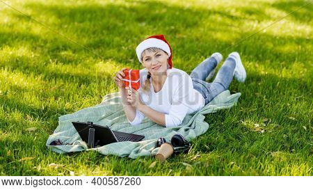 Laughing Girl Chatting With Parents. Christmas Online Congratulations. Happy Woman In Santa Hat Gree