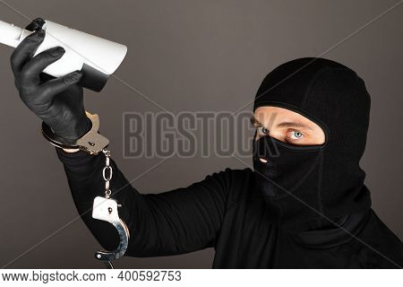 Picture Of Thief Wearing Black Face Mask Is Trying To Turn Off A Surveillance Camera