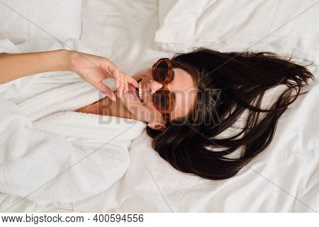 Young Gorgeous Smiling Woman With Dark Hair In White Bathrobe And Sunglasses Dreamily Bite Finger Ly