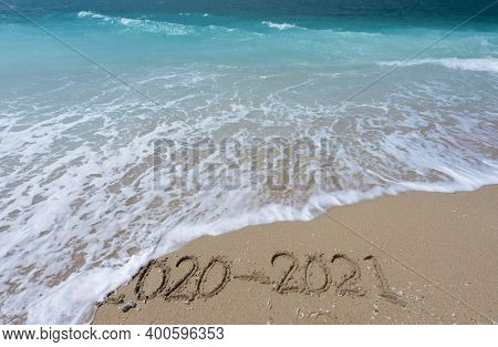 New Year 2021 is coming concept - inscription 2020 and 2021 on a beach sand,