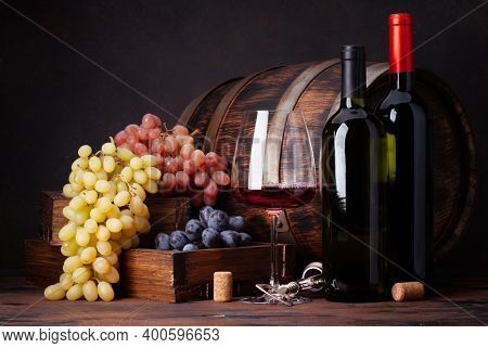 Wine bottles, grapes, glass of red wine and old wooden barrel. With copy space