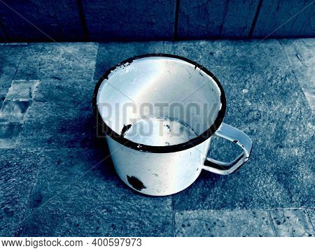 An Old Large Mug With Broken Enamel, Against The Background Of Old Boards, With A Spectacular Combin