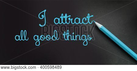 I Attract All Good Things - Positive Affirmation Words - Handwriting On A Black Paper With Blue Penc
