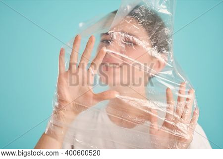 Upset Girl Choking In Plastic Bag Sadly Looking In Camera Over Colorful Background Isolated