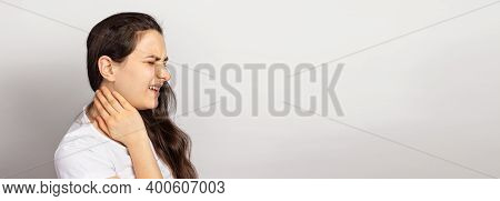The Woman Had A Neck, Muscle Cramp And Tension. A Banner With A Place For Text On A Light Background