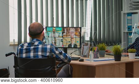 Paralysed Manager In Wheelchair Talking With Mask And Visor During Videocall Having Online Conferenc
