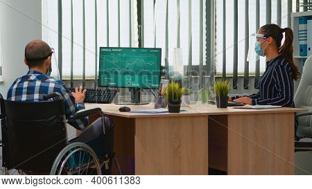 Woman Entrepreneur Bringing Immobilized Businessman At Workplace With Wheelchair Wearing Protection