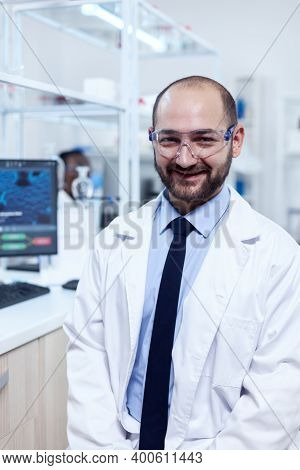 Young Biochemistry Scientist Wearing Protective Glasses Smiling At Camera. Serious Expert In Genetic