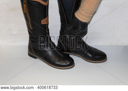 Legs Shod In Black Winter Boots. A Leather-gloved Hand Fastens The Zipper On The Second Boot.