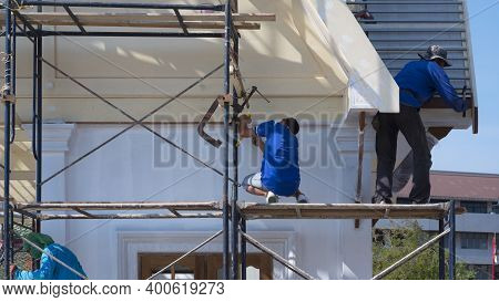 Asian Builder Workers With Work Tools On Scaffolding Are Working To Renovate External Structure Of T