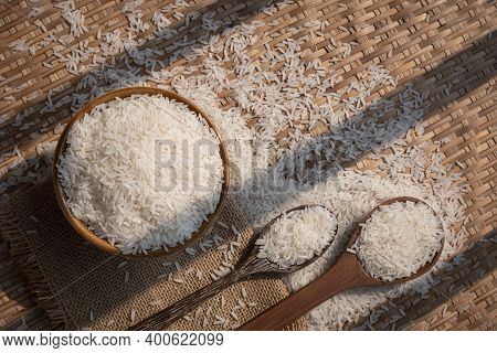 Sunlight And Shadow On Surface Of White Rice (thai Jasmine Rice) In Ceramic Bowl With Wooden Spoons