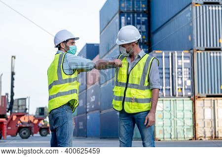 Two Cargo Container Workers Or Engineer Men Show Greeting Together With New Normal Style By Touching