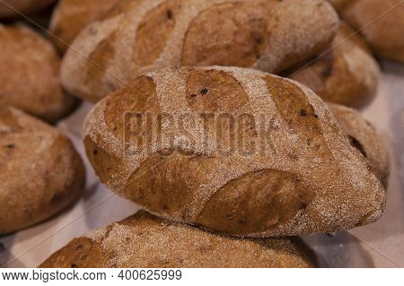 Freshly Baked Bread Sprinkled With Sesame Seeds On The Counter Of A Bakery.