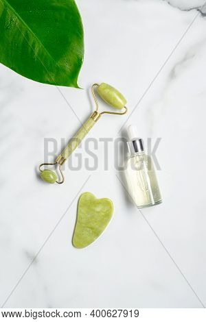Jade Roller With Natural Anti Aging Jade Stone, Essential Oil Dropper Bottle And Green Leaf On Marbl