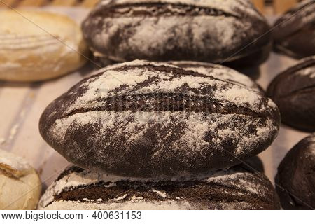 Freshly Baked Dark Bread Sprinkled With Sesame Seeds On The Counter Of A Bakery.