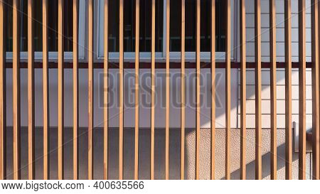 Sunlight On Surface Of Wooden Lath In Vertical Pattern In Front Of Glass Windows With White Artifici
