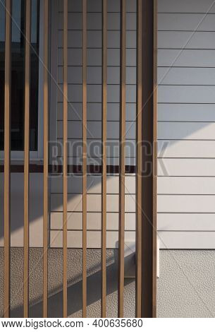 Sunlight And Shadow On Surface Of  Wooden Lath In Front Of White Artificial Wood And Gray Sheetrock