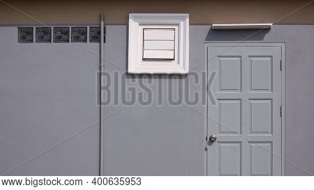 Front View Of Gray Wooden Door, Square Ventilation Shutter, Glass Blocks And Fluorescent Light Bulb