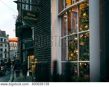View Of Traditional Christmas Tree In Cosy Room Behind Window With British Street Scene At Sunset, L