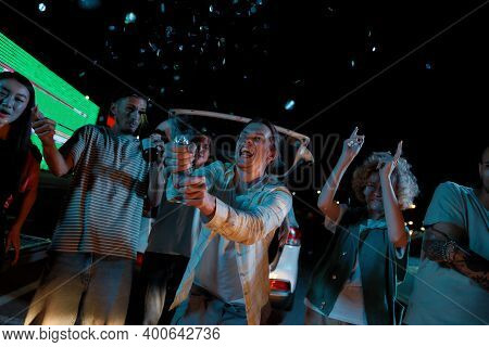 Hanging Out. A Well-dressed Young White Long Haired Man Opens A Confetti Cracker With His Friends On