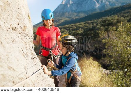 Mother Teaches A Child How To Use Safety Equipment. A Boy In A Helmet Goes Through Via Ferrata. A Wo