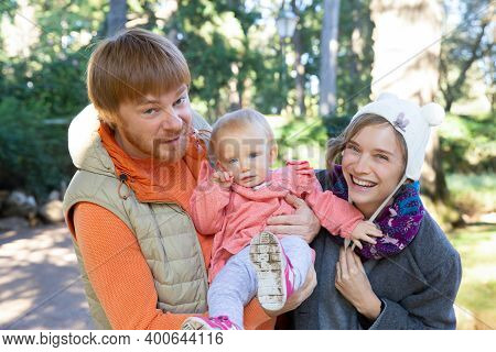 Cheerful Couple Of Parents And Toddler Daughter Having Fun While Walking Outdoors, Looking At Camera