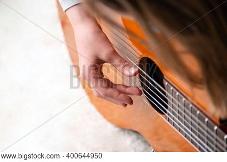 Close Up Of Hand Playing Acoustic Guitar. Practicing Classic Musical Instrument. Home School Educati