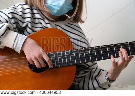 Close Up Of Musician Wearing Medical Face Mask And Playing Guitar. Concept Of Performance And Festiv