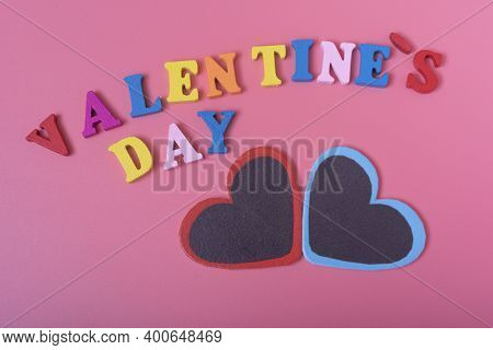 The Word Valentine's Day And Two Hearts On A Pink Background.