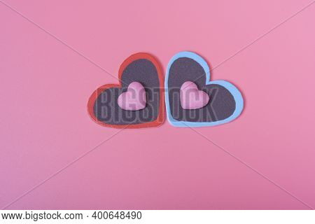 Two Hearts On A Pink Background In The Center And Two Small Hearts. The Concept Of Valentine's Day.