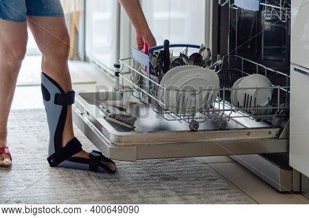 The Woman With A Orthotics On Her Foot Is Emptying The Dishwasher In The Kitchen