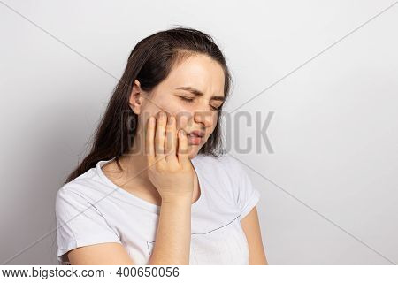 A Woman Holds A Sore Tooth With Her Hand. Dental Pain In Dentistry, Pulpitis And Tooth Decay, Nerve