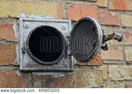Open Circular Heating Hood With Black Soot And Gray Iron Cover On The Brown Brick Wall Of The House